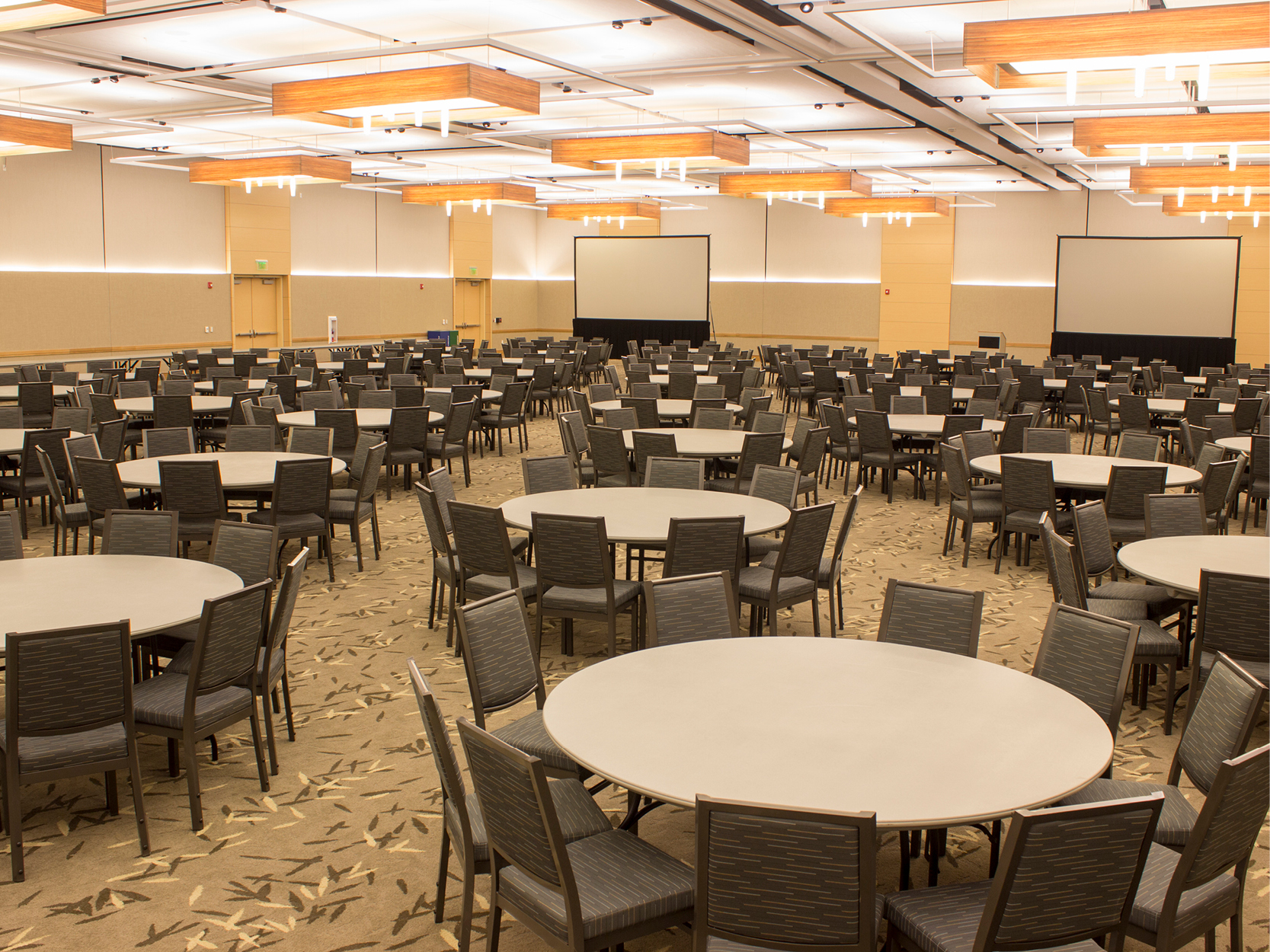 Ballroom with tables and chairs and two large screens